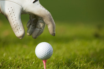 Human hand positioning golf ball on tee, close-up