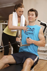 A young man exercising with a personal trainer