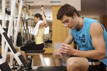 Portrait of young man taking a rest in gym