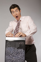 caucasian businessman with tie trapped in shredding machine
