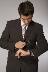 businessman looking on his watch with magnifying