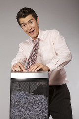 businessman with tie trapped in shredding machine
