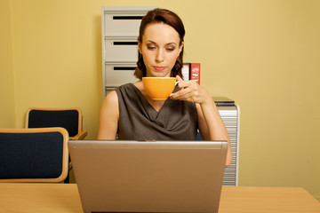 Businesswoman using laptop while having tea