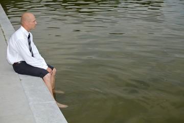 Businessman sitting on wall by lake