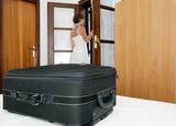 Woman arriving in simple pension bedroom poster