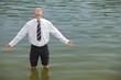 Businessman standing in lake, eyes closed