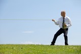 Businessman pulling rope in park