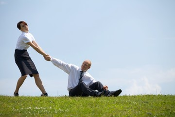 Businesswoman pulling businessman's hand in park