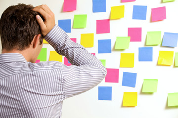 Businessman looking at wall of sticky notes with head in hands