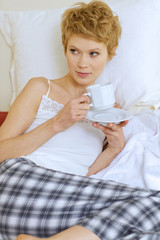 Woman drinking caffee in bed