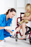 caring nurse bandaging little girls ankle in wheelchair