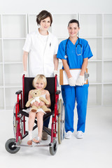 nurse and doctor with little girl in wheelchair