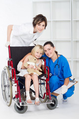 doctor, nurse and little girl patient in wheelchair