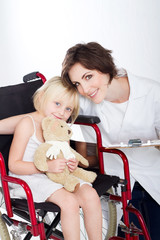 caring nurse and smiling girl in wheelchair