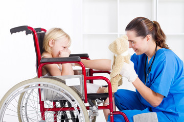 nurse cheering up little girl in wheelchair