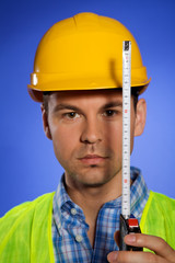 Portrait of architect in hardhat holding tape measure