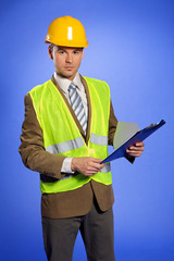 Portrait of businessman in in coveralls using clipboard
