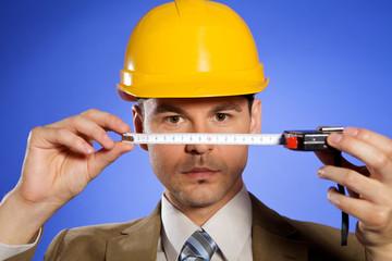 Portrait of businessman in hardhat holding tape measure