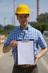 Portrait of architect holding clipboard at construction site