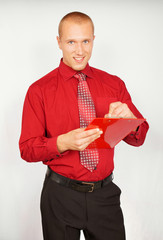 Young businessman in red shirt writes document.