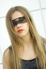 Beautiful fashionable girl. Blindfolded black lace ribbon