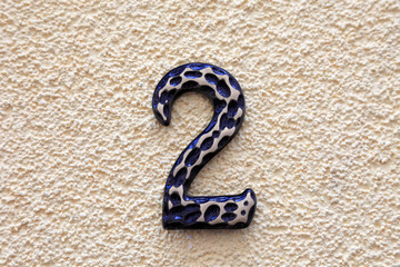 Number two made of metall on textured surface.