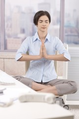 Female office worker meditating at work
