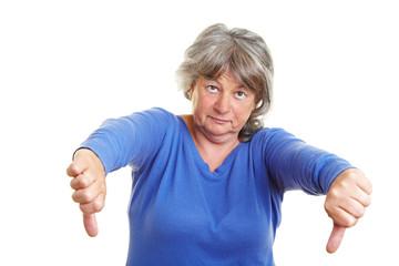 Seniorin zeigt mit Daumen nach unten