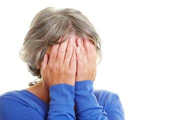 Seniorin hält sich Hände vor Gesicht