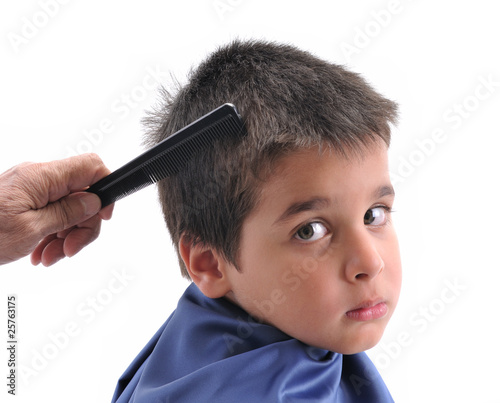 Cute boy having haircut on white background.