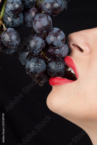 Detailed view of y young woman eating grapes isolated