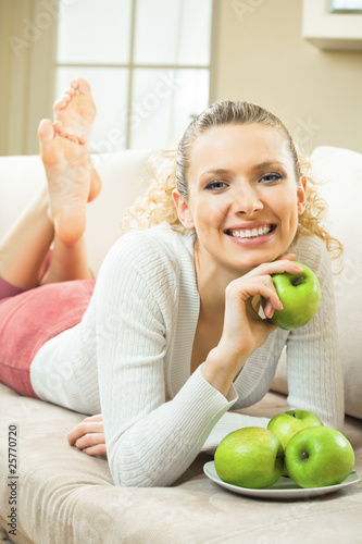 Young happy smiling woman with apples, at home
