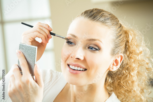 Young woman with mirror and makeup brush indoors