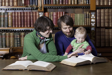 Happy family with a child reading in classic library