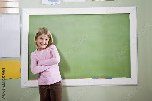 School girl in classroom standing by blackboard