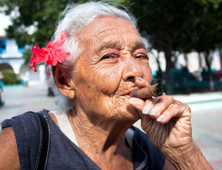 Old wrinkled woman with red flower smoking cigar.  Cuba