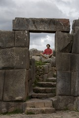 A Young Man Meditates In Ancient Incan Ruins Outside Cuzco,Peru