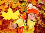 Fototapety Child in autumn orange leaves.