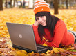 Girl in autumn orange leaves with laptop.Fall sale.