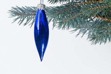 blaue Glastrofen mit godenem Glitter hängt an einer Silberfichte