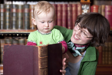 A young mother with a baby reading a book