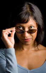 Indian woman peeking over sunglasses