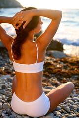 Beautiful brunette sunbathing on the beach