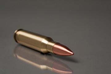 gun bullet lie on a grey bg