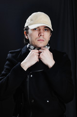 Man in baseball cap and coat. Black background.