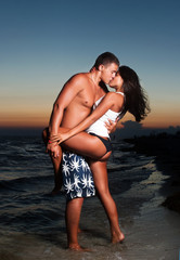 Happy kissing pair against a sunset
