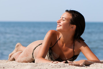 Young and sensual woman enjoying a sunny day on beach