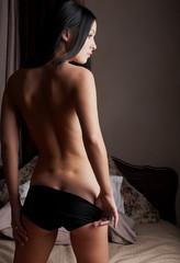 Young brunette woman in her bedroom