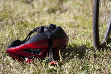 casque rouge posé à l'envers, près d'une roue