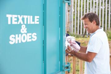 Man At Recycling Centre Disposing Of Clothing